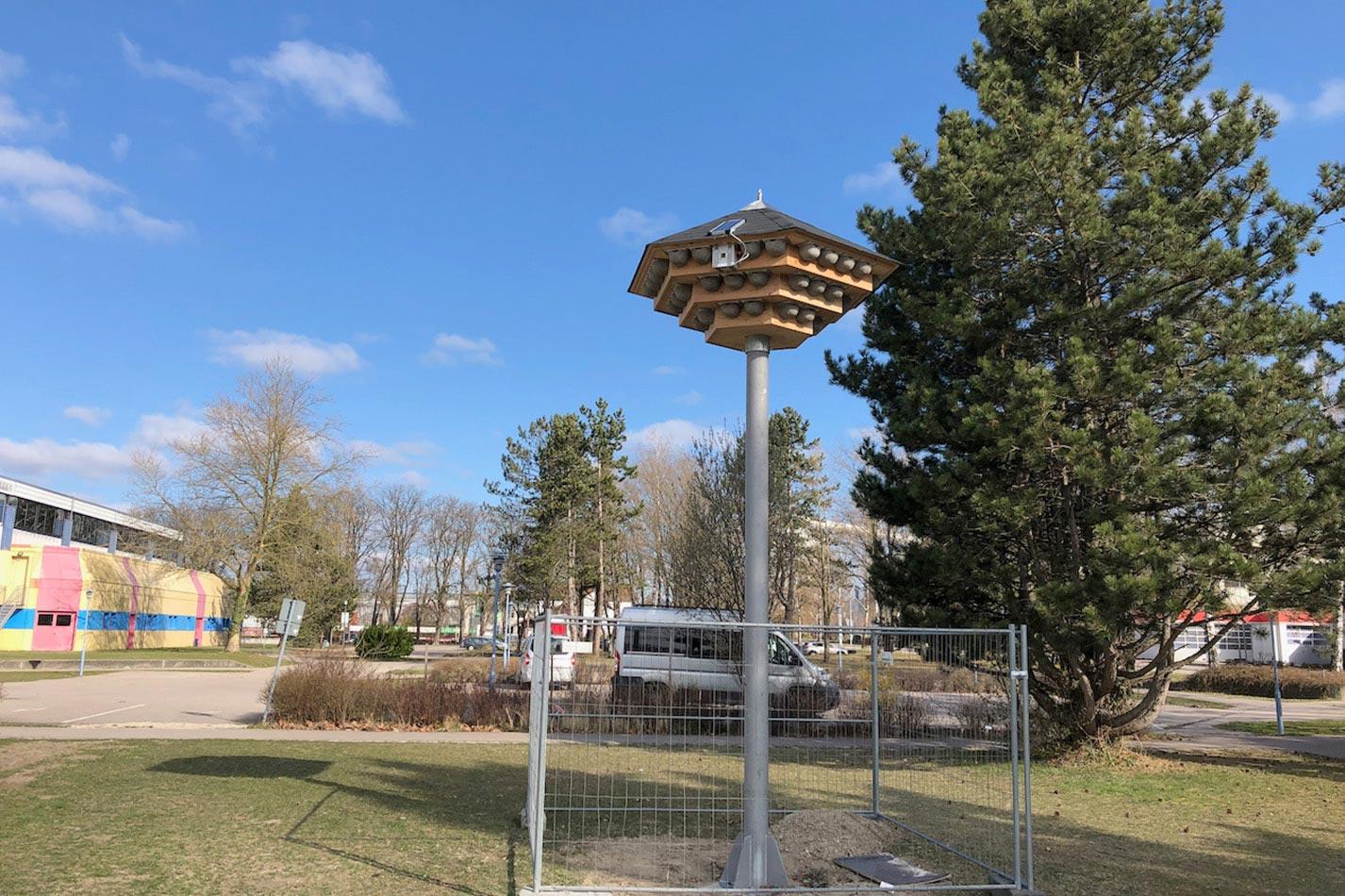 Ein dreistöckiges Schwalbenhaus aus Holz mit Kunstnestern für Mehlschwalben auf einem Stahlmast mit einer Klangattrappe auf einer Wiese