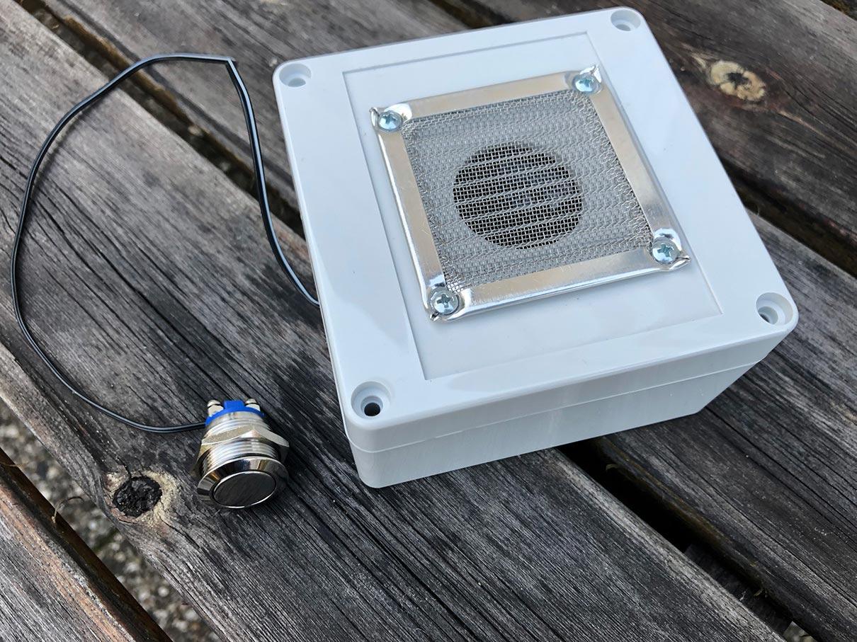 Geräuschmodul aus wasserfestem Gehäuse mit Stecker auf einer Holzunterlage