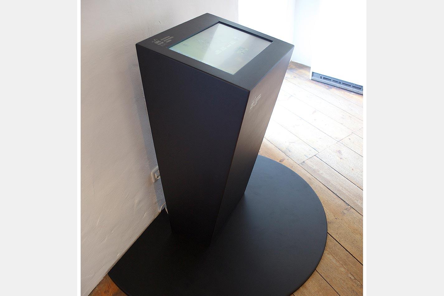 Touchscreen Stele vor einer weißen Wand von der Seite fotografiert