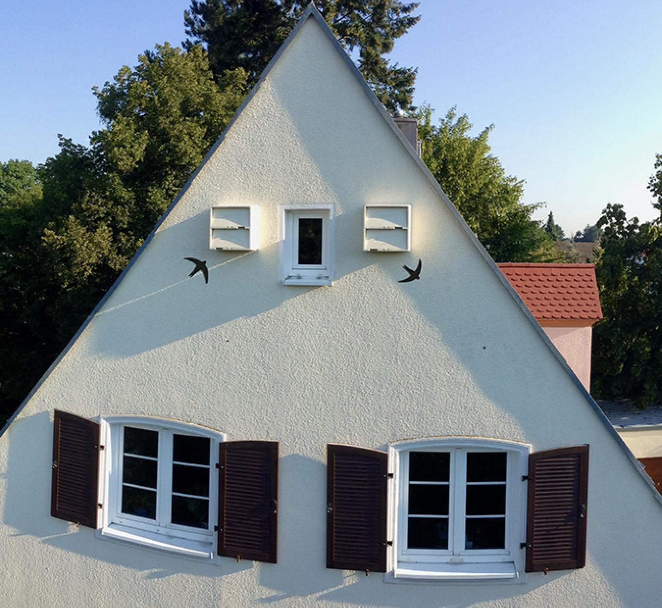 Mauerseglerkasten an gelber Hausfassade  mit Zeigevogel