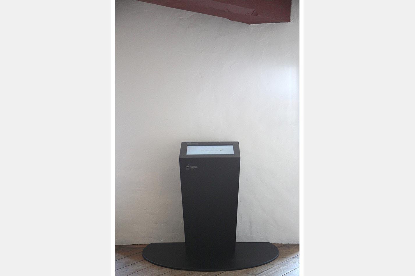 Touchscreen Stele vor einer weißen Wand aus lackiertem dunklen Holz
